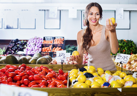 Positive smiling young woman buying fresh lemons on marketplace