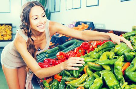 Positive female customer choosing fresh paprika on market
