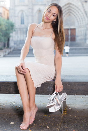 portrait of young smiling russian adult girl in evening  apparel sitting  with sandals in european town