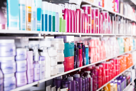 showcase with bottles of shampoos and conditioners in the hair care store. Archivio Fotografico