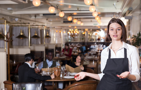 Smiling young waitress warmly welcoming to cozy modern restaurant Stock Photo