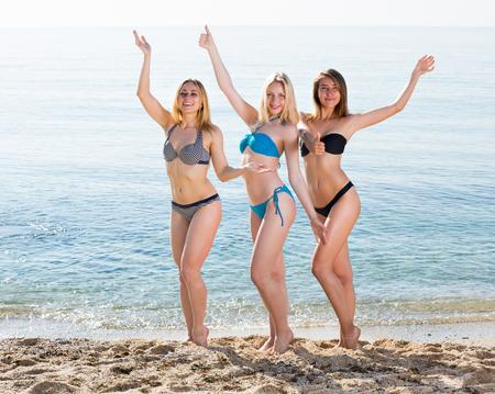 three smiling attractive young women posing in bikini on sandy beach