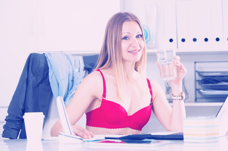 Sexy woman in red bra pretending to work on laptop