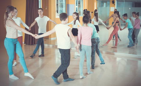Group of tweens exercising folk dance, forming circle with female trainer in choreography class