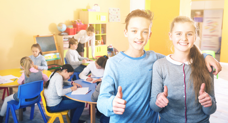 Two satisfied smiling positive   children standing in schoolroom on background with pupils studying with teacher