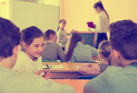 Happy pupils chattering sitting on back desks at lesson in elementary school Stock Photo