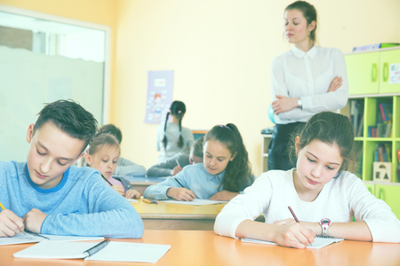 Group of school kids with pens and notebooks studying in classroom with teacher Imagens - 100209089