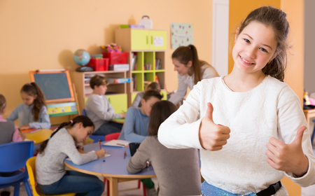 Portrait of smiling schoolgirl and children drawing in classroom Фото со стока