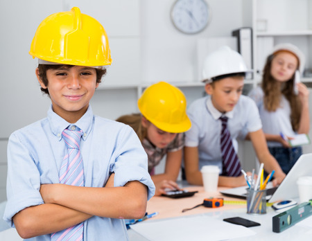 Teen boy in color helmet builder with collective architects near laptop