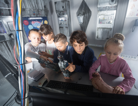 Curious children discuss the game  in bunker quest room