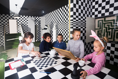 Curious  kids discuss the game in the chess quest room