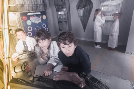 Friendly children are concentrating on finding a way out of bunker escape room
