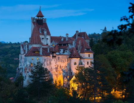 View of main romanian tourist attraction Bran Castle on cliff top on twilight