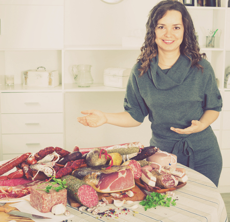 Young happy smiling positive woman costs near table on which sausages and smoked meat lie