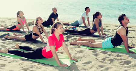 Group of sporty people practicing various yoga positions during training on beach Foto de archivo