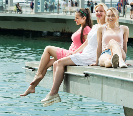 Portrait of three young girls resting at mediterian seaside in harbour with smilling faces on vacation