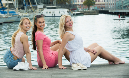 Three smilling girls sitting on dock pier while spending vacation time in Catalonia 免版税图像