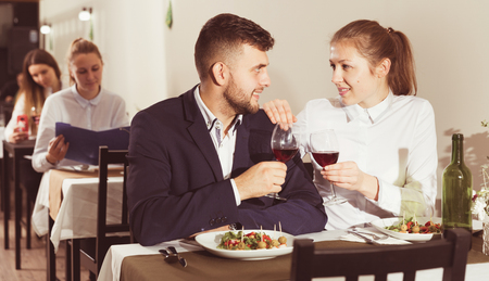 Gentleman with elegant woman are having dinner in luxury restaurante indoor.