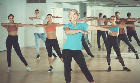 positive men women of different ages posing in fitness studio