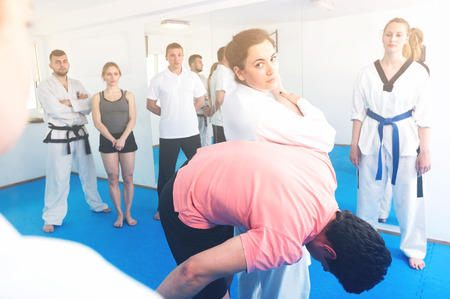 Smiling woman is showing new submission hold to adults in taekwondo class.  Stock Photo
