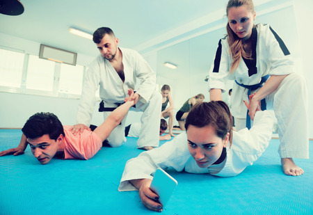 Woman is taking selfies while training in pairs at taekwondo class.