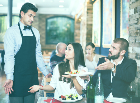 Adult couple expressing dissatisfaction with a waiter about food