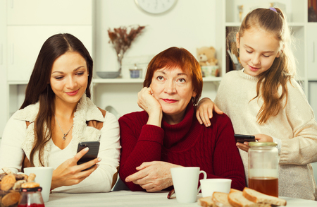 Bored grandma sitting at home table while daughter and granddaughter absorbedly looking at phones