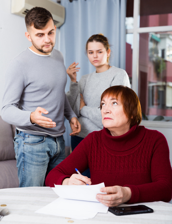 Serious adult son and daughter controlling elderly mother signing of documents at home