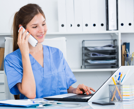 Female doctor working with laptop in office advising patient on phone