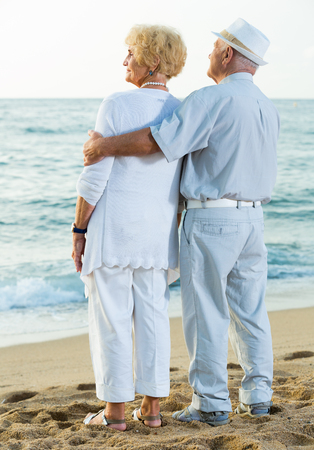pensioners woman and man in hat standing back on the sea shore