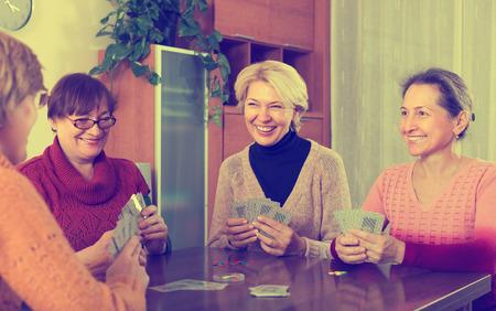 Happy elderly women having fun with pack of cards indoor Standard-Bild