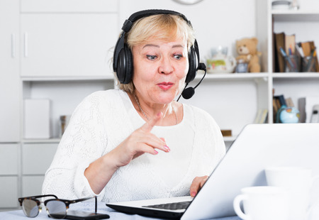 Mature woman communicates via the Internet with friends or relatives Stock Photo