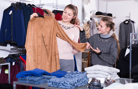 Nice girl and her young mother satisfied with purchases in clothing shop Stock Photo - 100484756