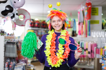 Positive girl looking for funny things in store of festival outfits and accessories  Stock Photo