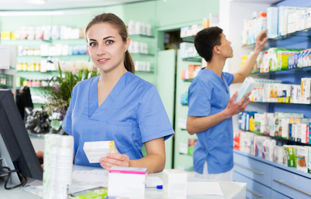 positive female and male specialist are attentively stocktaking medicines with notebook near shelves in pharmacy.