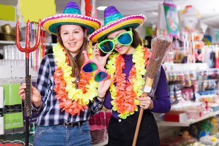Portrait of joyful comically dressed girls joking in festive accessories shop