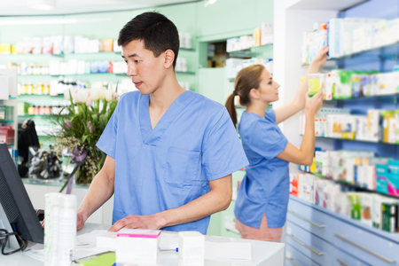 serious female and male specialist are attentively stocktaking medicines with notebook near shelves in pharmacy.