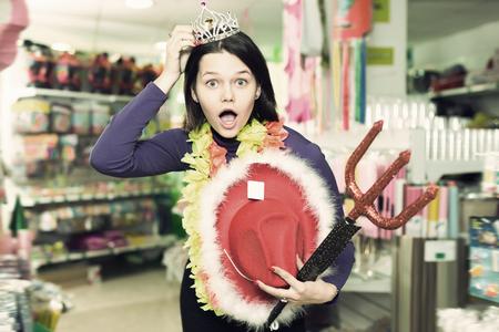 Portrait of joyful comically dressed girl joking in festive accessories shop