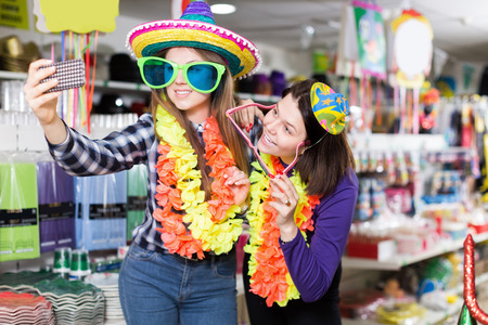 Comically dressed happy women friends making funny photo in carnival outfits shop