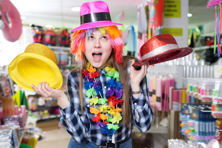 Laughing young woman preparing for party, choosing funny headdresses in store Stock Photo