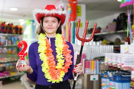 Portrait of modern comically dressed girl joking in festive accessories shop Reklamní fotografie