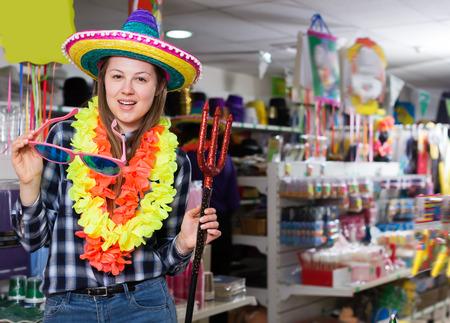 Portrait of happy comically dressed girl joking in festive accessories shop Reklamní fotografie