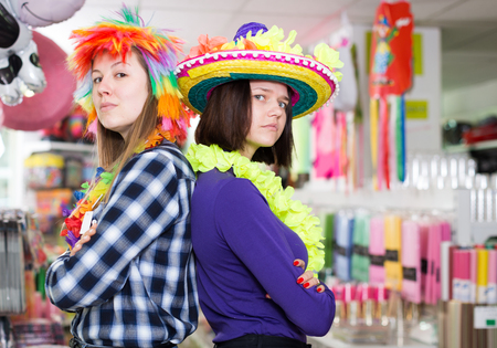 Portrait of comically dressed cheerful girls with crossed hands standing back to back in festive things shop