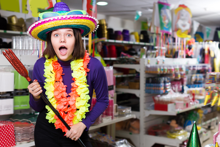Portrait of cheerful comically dressed girl joking in festive accessories shop