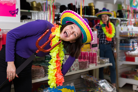 Positive girl  is trying funny things in store of festival outfits and accessories
