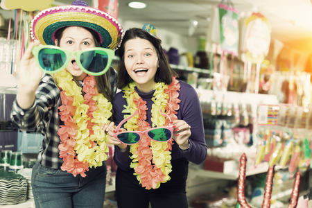 Portrait of glad comically dressed girls joking in festive accessories shop Stock Photo