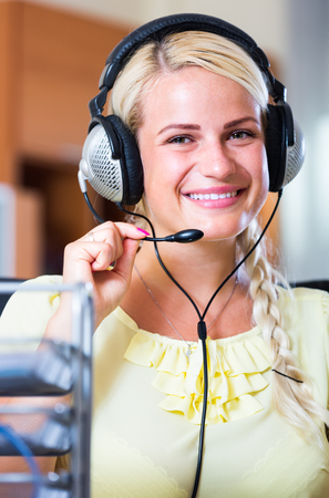young woman 20-35 years with headset working at laptop Stock Photo