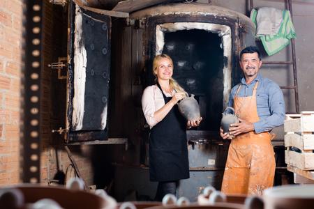 Smiling man and woman potters holding black glazed ceramic vases next to kiln
