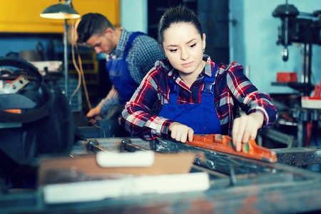 Girl master is standing near workplace and working with level in workshop