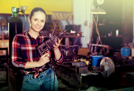Portrait of young female master standing with drill in workshop 写真素材